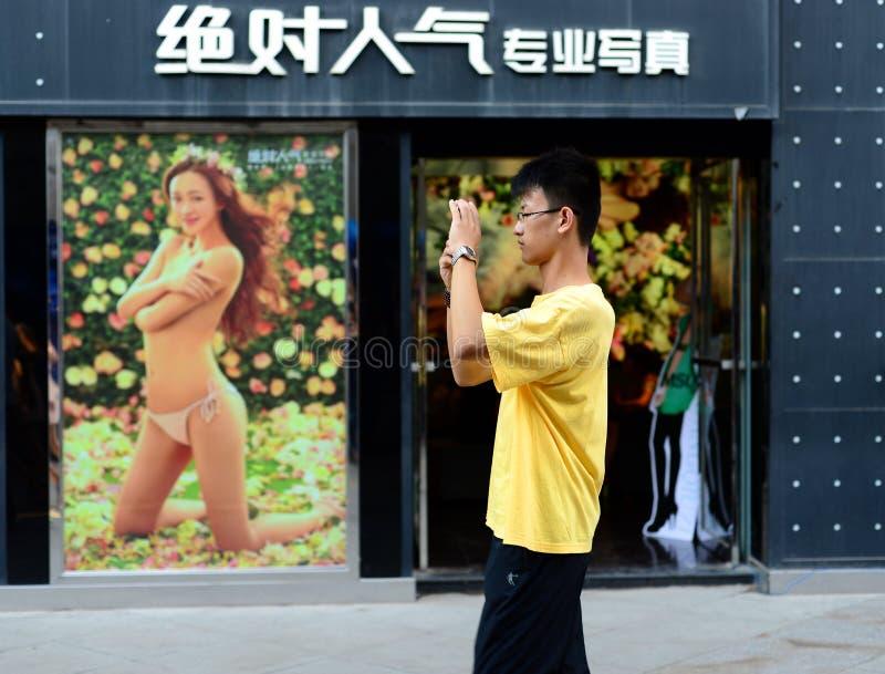 Xian, 8 China-Augustus, 2013: Een mens neemt een foto buiten een boudoirstudio in China stock foto's