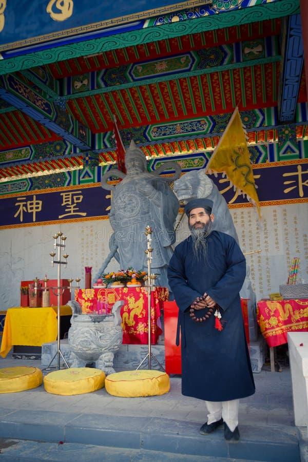 XIAN KINA - SEPTEMBER 06, 2013: Den medelåldersa Taoistprästen bär en fin svart Manchurian hatt och ett traditionellt djupblå arkivfoton