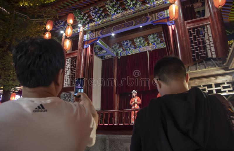 Tourists watching Chinese Opera singer onstage. Xian, Shaanxi, China - September 9, 2018 : Tourists recording female Chinese Opera singer in traditional costume royalty free stock photography