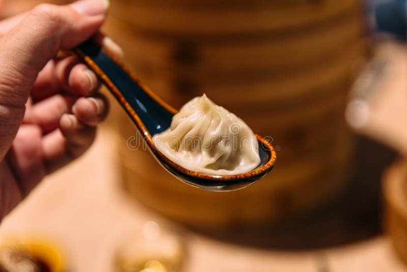 Xiao Long Bao Soup Dumpling en cuchara con la cesta de bambú de la flámula de la falta de definición en fondo fotos de archivo