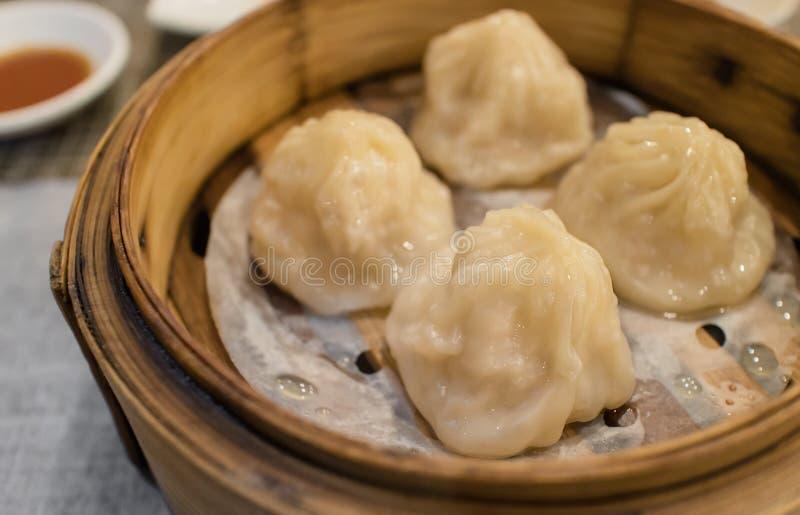 Xiao Long Pao en pequeña cesta de cocido al vapor al vapor de bambú, tipo de bollo cocido al vapor chino llenado de la langosta,  fotografía de archivo libre de regalías