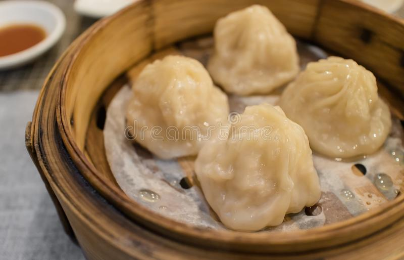 Xiao Long Pao in piccolo canestro di cottura a vapore di bambù, tipo di panino cotto a vapore cinese riempito di interno dell'ara fotografia stock libera da diritti