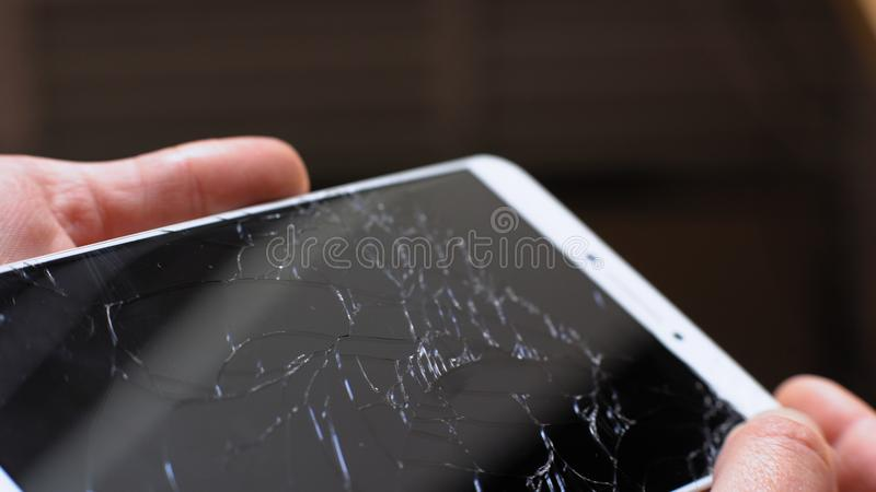 Xiaomi MI Max broken phone turning in hands. Man holding Xiaomi MI Max smartphone with broken screen in his hands. He is turning phone on sunlight to see stock photo