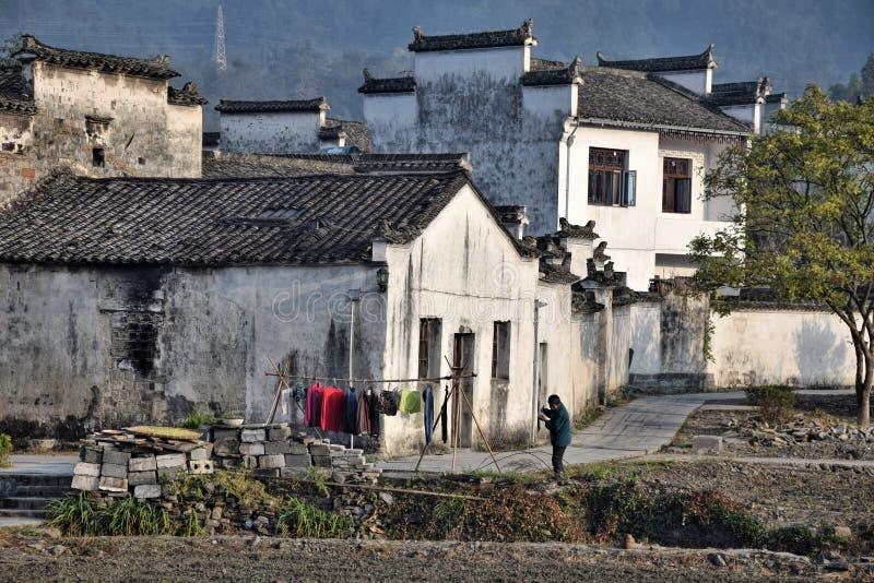 """XIDI, PROVÍNCIA de ANHUI, †de CHINA """"CERCA DO outubro de 2017: Uma mulher que come seu café da manhã na frente de sua casa em X imagens de stock royalty free"""