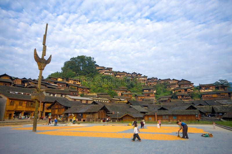 Xijiang Miao Minority Village Town Square Houses. Xijiang, China - September 15, 2007: Villagers drying corn at the town square below the gorgeous wooden stock images