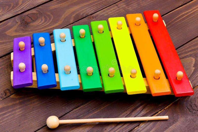 Xilófono en la tabla de madera marrón vieja Xilófono del ` s de los niños, pintado en los colores del arco iris fotos de archivo libres de regalías