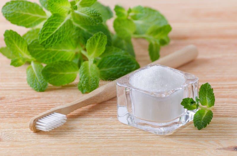 Xilitol natural alternativo de la crema dental, soda, sal, y cepillo de dientes de madera, menta en de madera imagenes de archivo