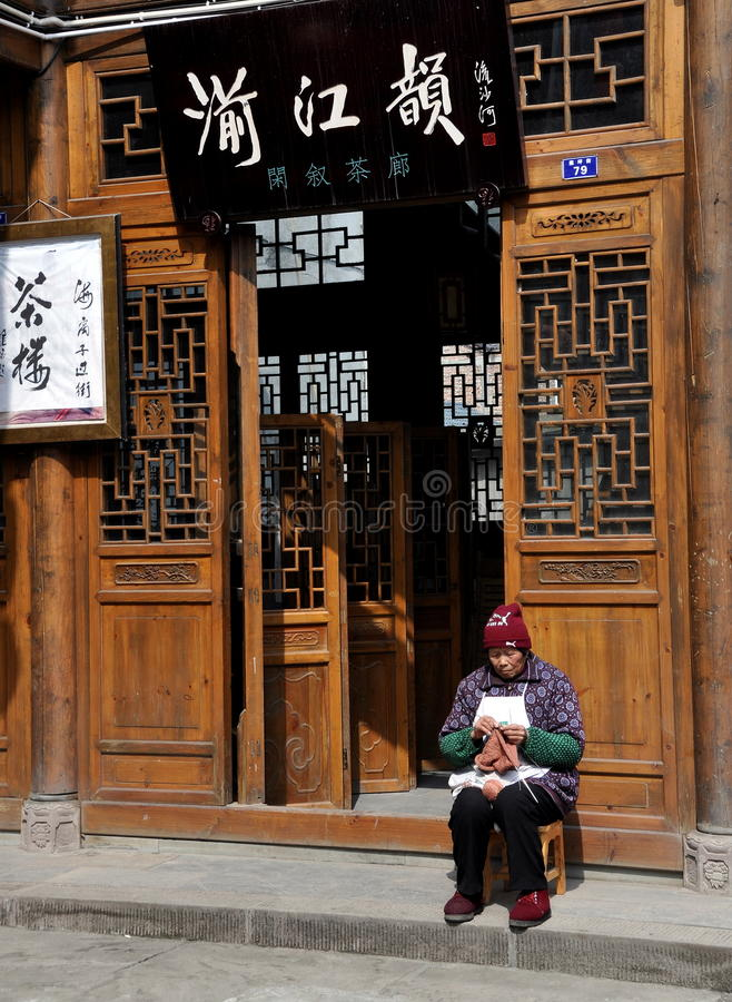 Xin Xing Zhen, China: Old Woman Knitting. An old woman wearing a stocking knit cap and mismatched shoes knits in front of a beautiful wooden lattice-work doorway royalty free stock photography