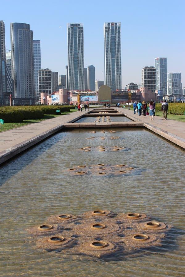 Xinghai fyrkant cityscape Skyskrapabyggnad med springbrunnen i förgrunden i Dalian Kina fotografering för bildbyråer