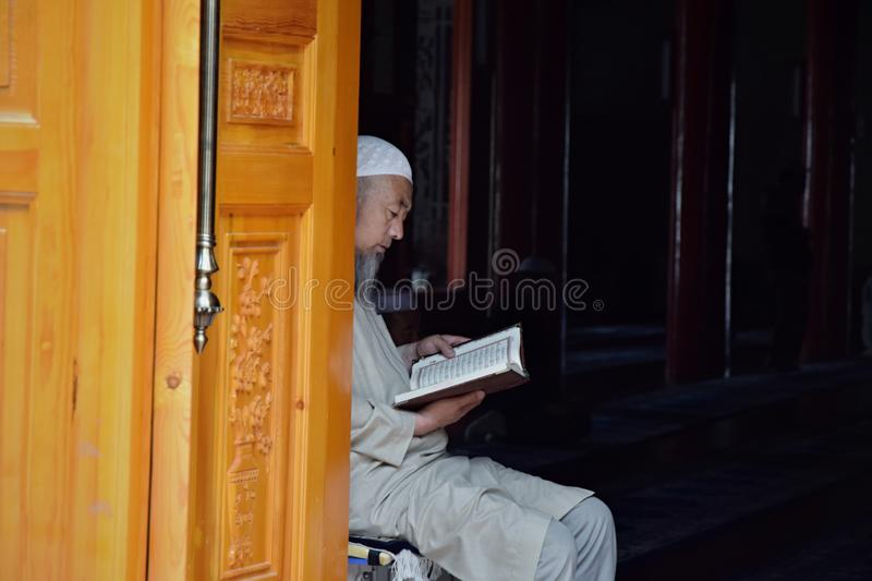 XINING, QINGHAI PROVINCE, CHINA - CIRCA SEPTEMBER 2019: A man sitting and reading a book inside Great Dongguan Mosque in Xining. royalty free stock photos