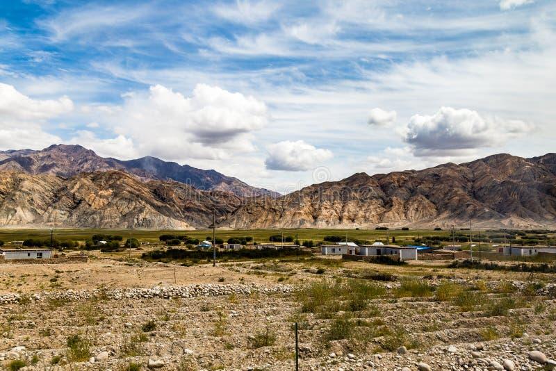 Xinjiang, China: local villages and mountains on the Pamir Plateau along Karakorum Highway, near Tashkurgan. Connecting Kashgar and the Pakistan Border, this royalty free stock photo
