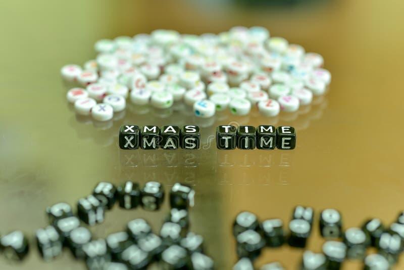 XMAS时间写与与白色字母表小珠的丙烯酸酯的黑立方体在玻璃背景 免版税库存照片