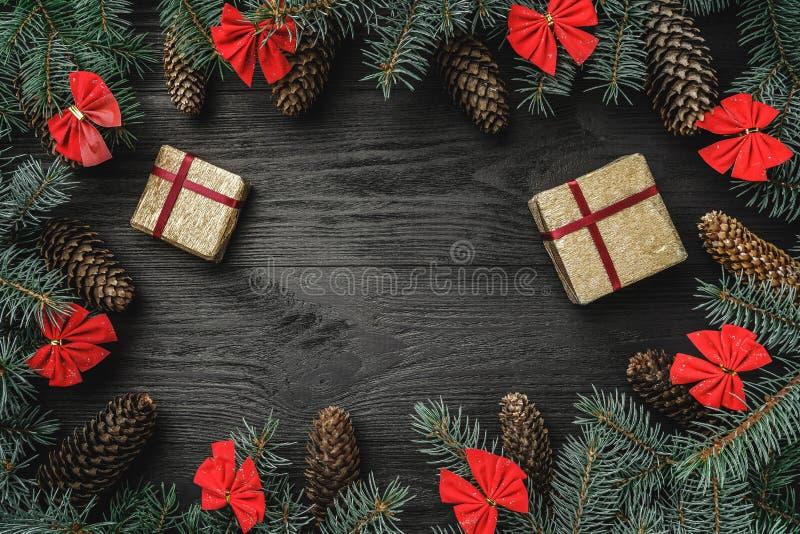 Xmas贺卡 冷杉分支与锥体和红色碗,在黑木背景 圣诞节礼物weihnachtspakete 免版税库存照片