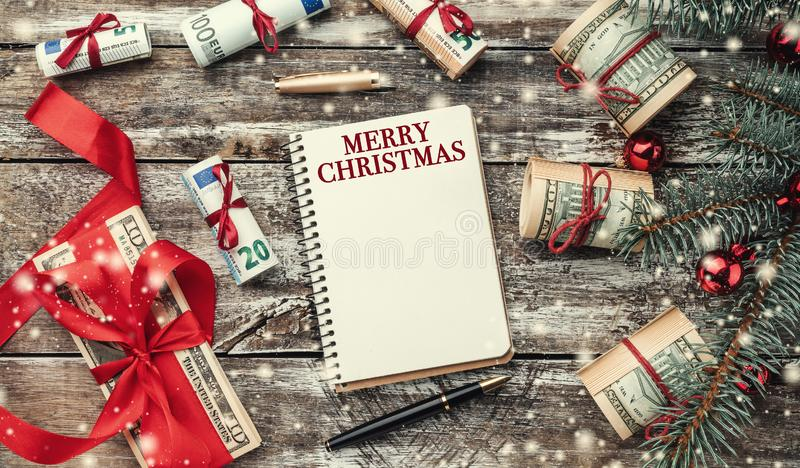 Xmas background of old wood. Christmas tree with American and European money. Holiday Gifts. Top view stock image