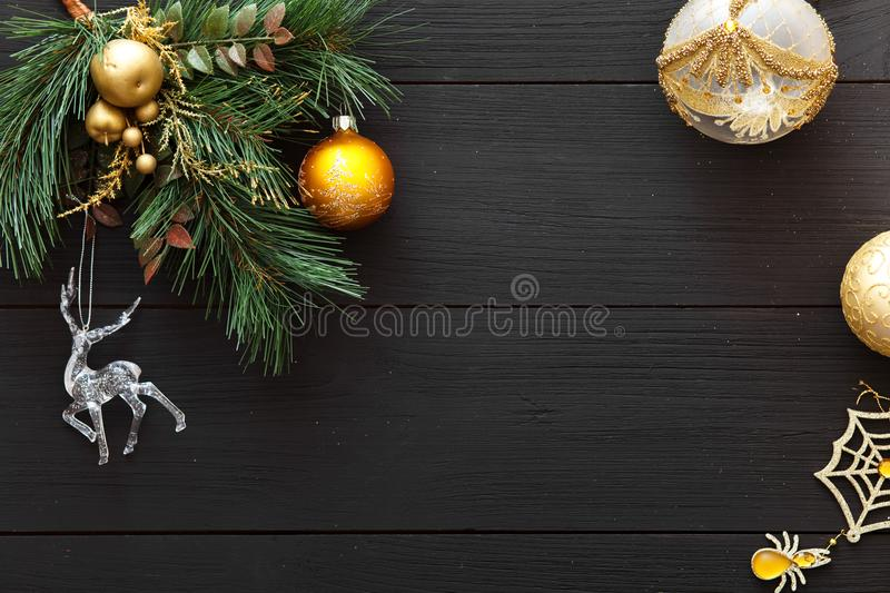 Xmas balls on merry Christmas tree, happy new year card decoration on black wooden background, top view, copy space stock image