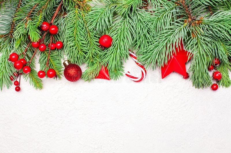 Xmas border with green Xmas fir branch, red holly berries and baubles on white stucco plaster texture background. Christmas composition, top view flat lay with royalty free stock photo