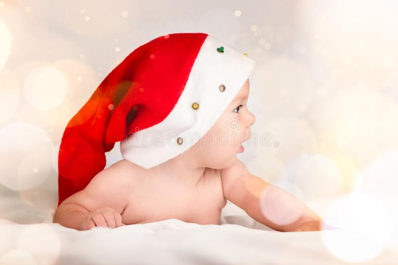 Xmas card with cute baby girl with santa hat on beige airy briht background with copy space stock image