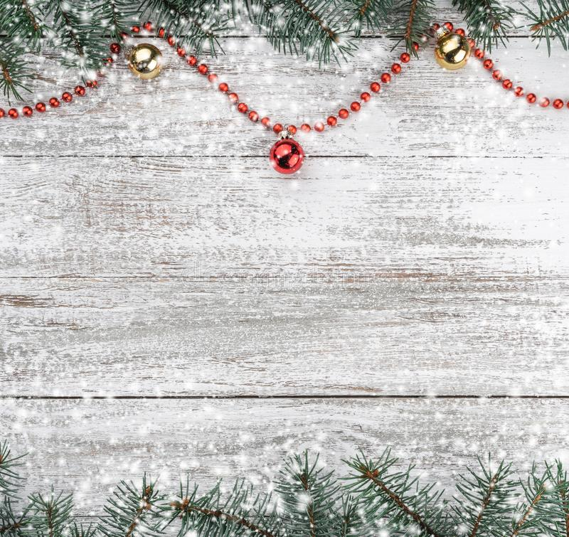 Xmas card. Old wooden Christmas background. Fir branches. Gold and red baubles. Red garlands. Top view. Space for your text. Snow effect royalty free stock images
