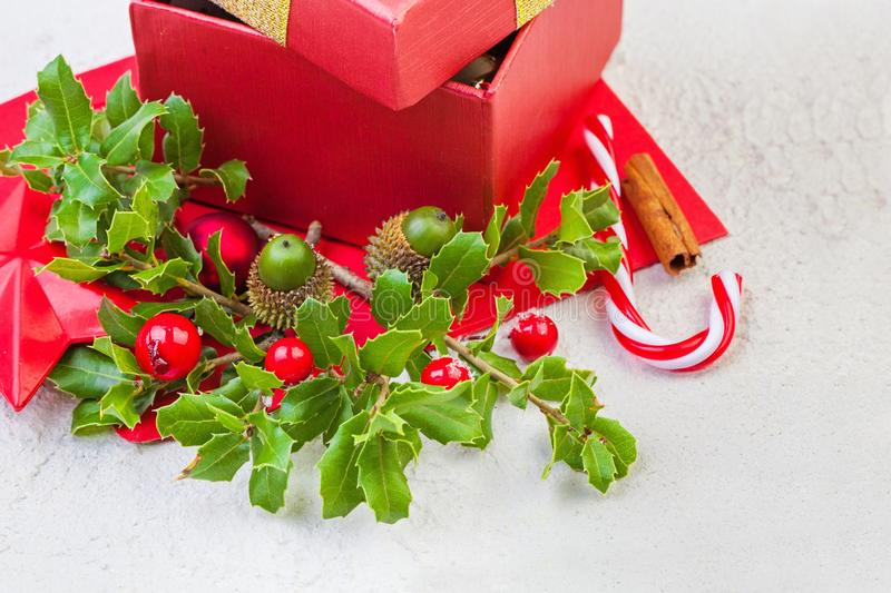 Xmas concept with winter holly leaves, red berries and gift.  royalty free stock photos