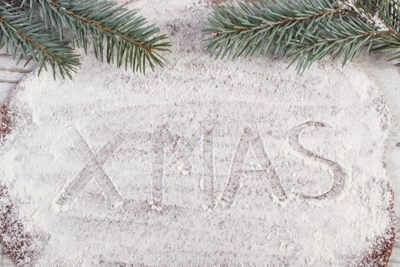 Xmas da inscrição escrito na farinha na massa para o pão-de-espécie e ramos spruce, conceito do tempo do Natal foto de stock royalty free