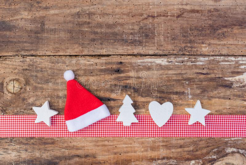 Christmas greeting card decoration with red santa hat and ornaments on red ribbon border and wood background royalty free stock image
