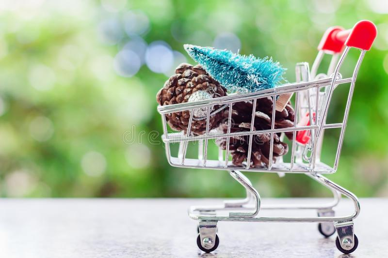Xmas decorative items in mini shopping cart or trolley against b stock photography