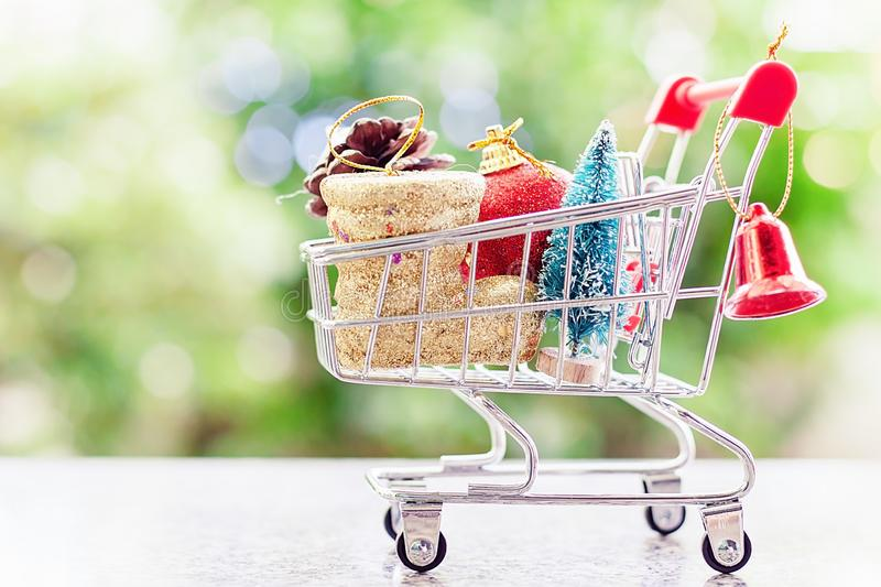 Xmas decorative items in mini shopping cart or trolley against b royalty free stock photos
