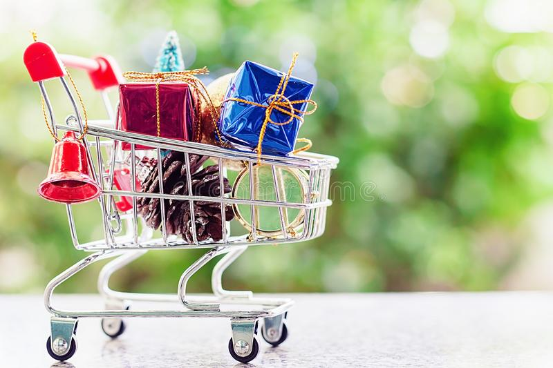 Xmas decorative items in mini shopping cart or trolley against b royalty free stock photography