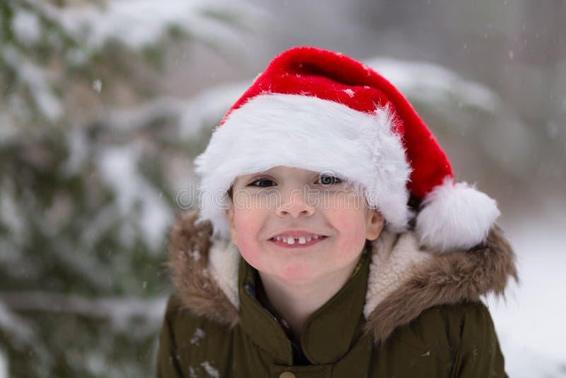Xmas feliz e ano novo Menino de sorriso feliz no chapéu vermelho de Santa Foto exterior do inverno Conceito do Natal e do ano nov imagem de stock royalty free