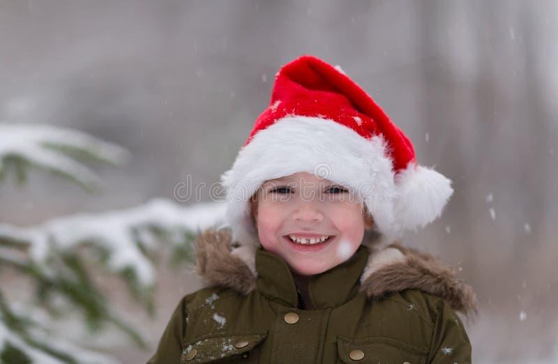 Xmas feliz e ano novo Menino de sorriso feliz no chapéu vermelho de Santa Foto exterior do inverno Conceito do Natal e do ano nov fotografia de stock royalty free