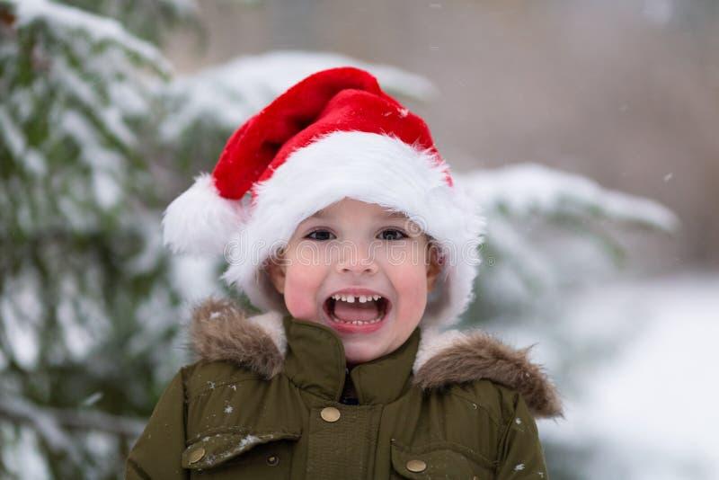 Xmas feliz e ano novo Menino de sorriso feliz no chapéu vermelho de Santa Foto exterior do inverno Conceito do Natal e do ano nov foto de stock royalty free