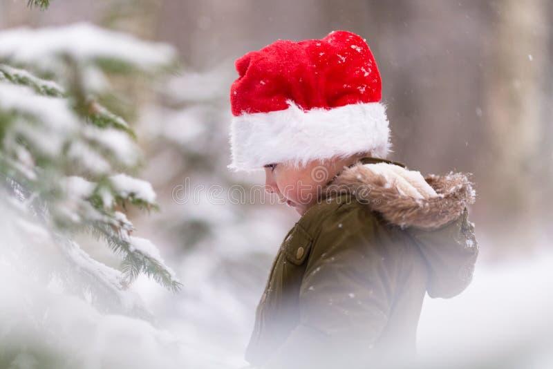 Xmas feliz e ano novo Menino de sorriso feliz no chapéu vermelho de Santa Foto exterior do inverno Conceito do Natal e do ano nov imagens de stock