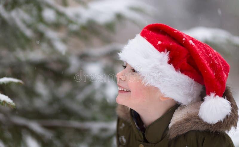 Xmas feliz e ano novo Menino de sorriso feliz no chapéu vermelho de Santa Foto exterior do inverno Espaço livre Copie o espaço Na fotos de stock royalty free