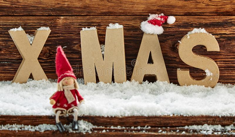 Xmas greeting card background with cute Santa doll. Sitting on winter snow with the letters - Xmas - behind against rustic wood stock images