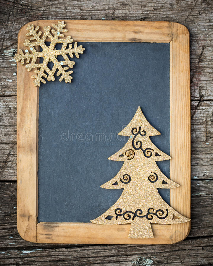 Xmas holidays card. Gold Christmas tree decorations on vintage wooden blackboard with copy space. Xmas holidays card stock image