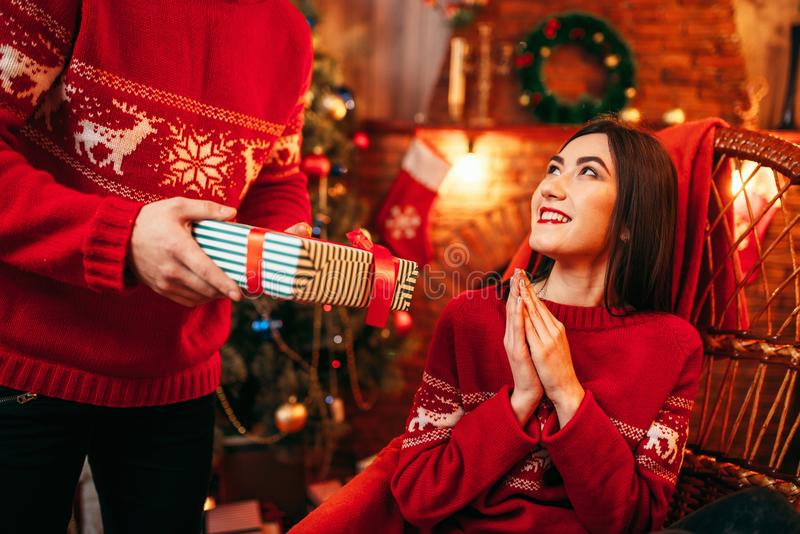 Xmas, male person makes gift to beautiful woman stock images
