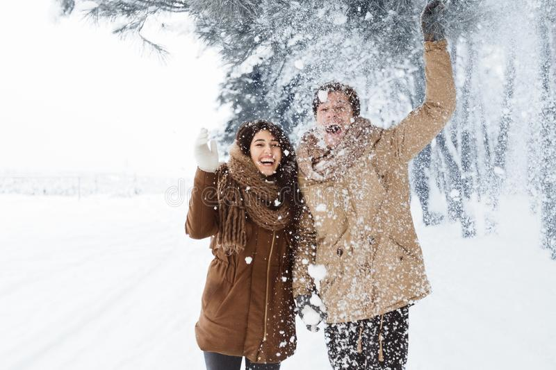 Happy Couple Throwing Snow Walking In Snowy Winter Forest stock images