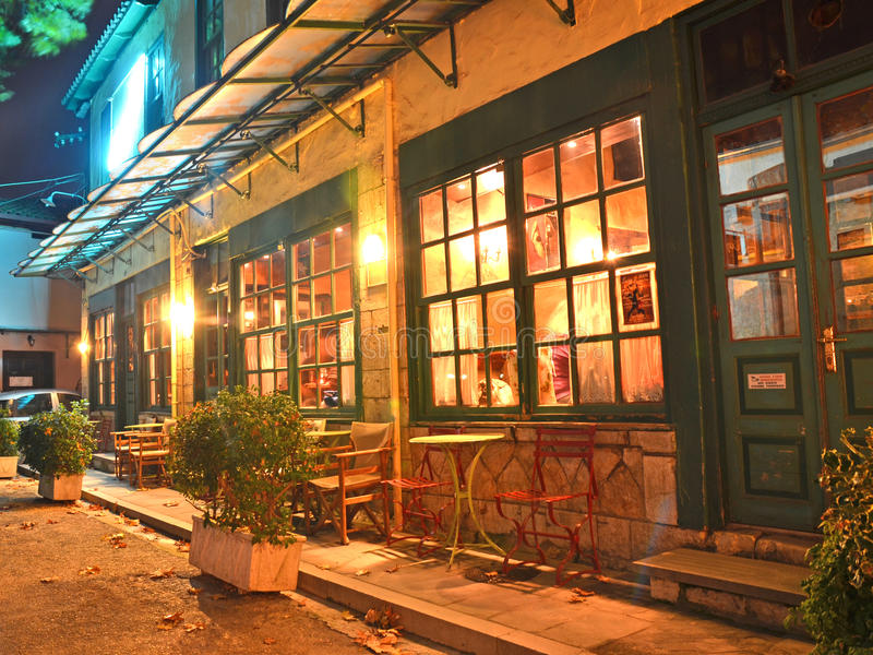 Xmas night street cafe ioannina greece. Lights tables chairs colors stock photography