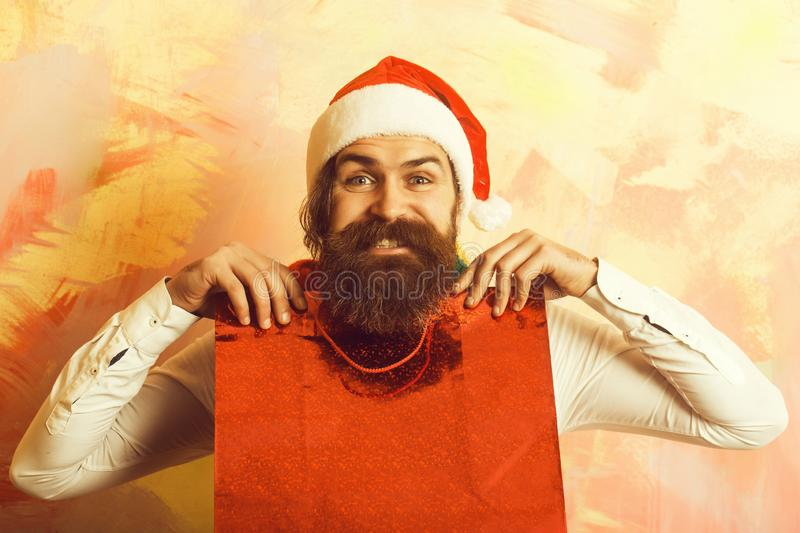 Xmas package or shopping pack. Santa claus man with present or gift. Christmas man with happy face. Holiday and celebration. New year guy with in scarf and hat royalty free stock images