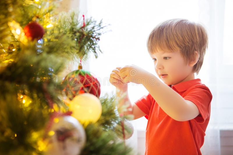 Xmas party celebration. Child decorating Christmas tree at home. Family with kids celebrate winter holidays. New year small boy at royalty free stock photography