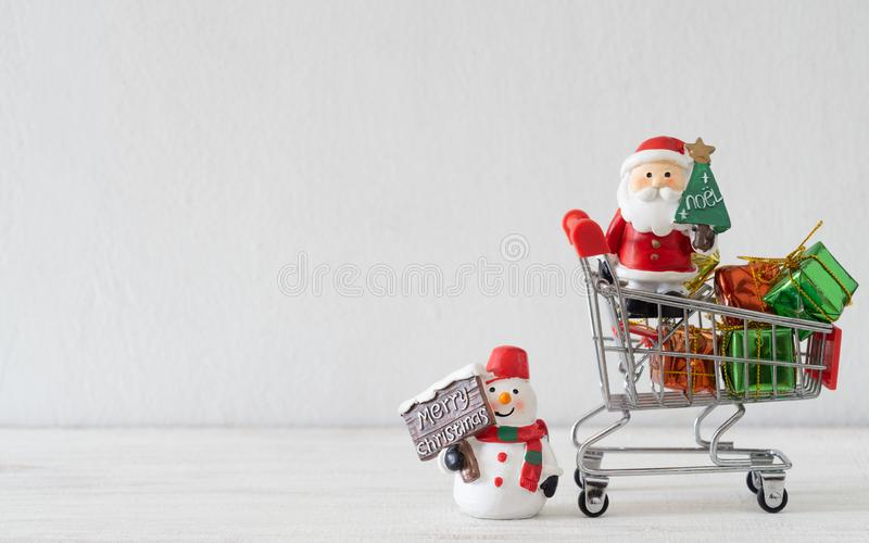 Xmas Shopping background concept. Santa Claus, Snowman and shopping cart full of presents on white background with copy space stock photos