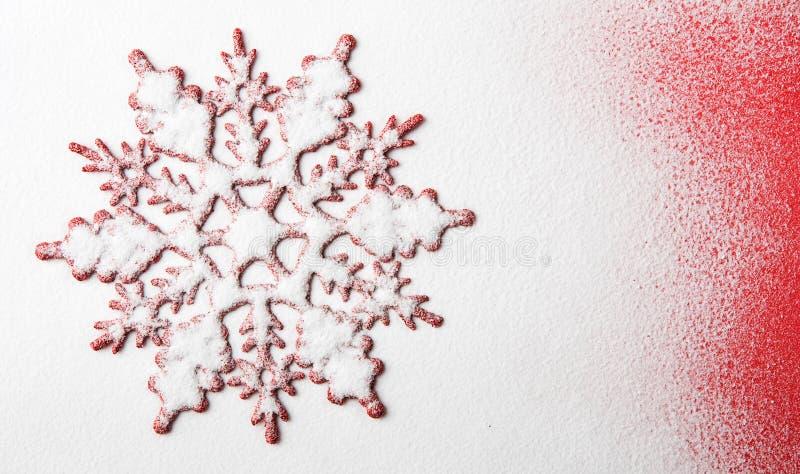 Xmas-snöflingaform på snön med röd bakgrund royaltyfri bild