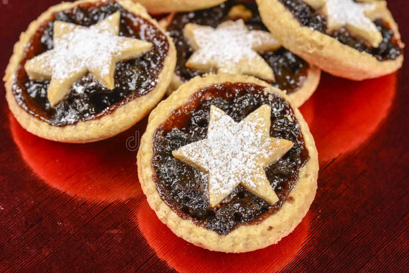Xmas star mince pies. Homemade Xmas mince pies on reflective red table mat royalty free stock images