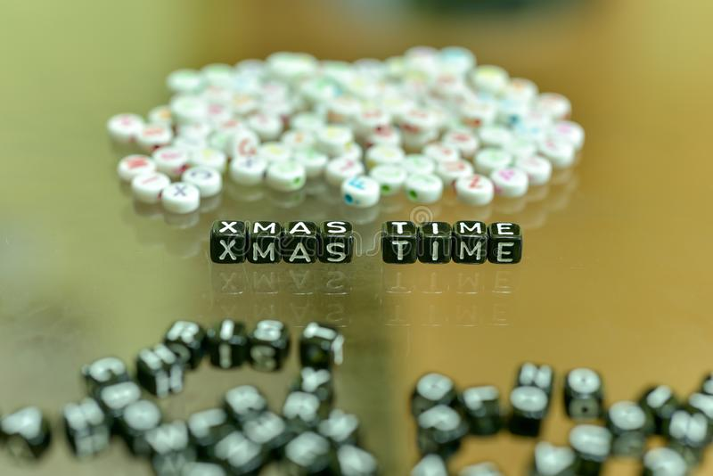 XMAS TIME written with Acrylic Black cube with white Alphabet Beads on the Glass Background.  royalty free stock photos