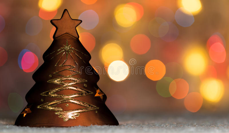 Xmas tree shaped candle holder standing in snow, with christmas tree lights, bokeh background and copy space. Festive banner royalty free stock photo