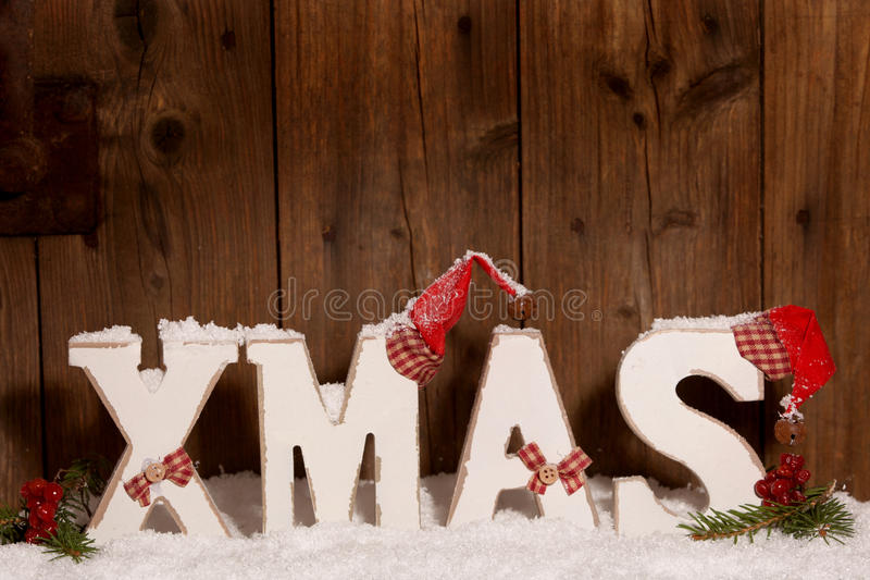 Xmas, Wooden letters with Christmas hats. In front of wooden background royalty free stock photos