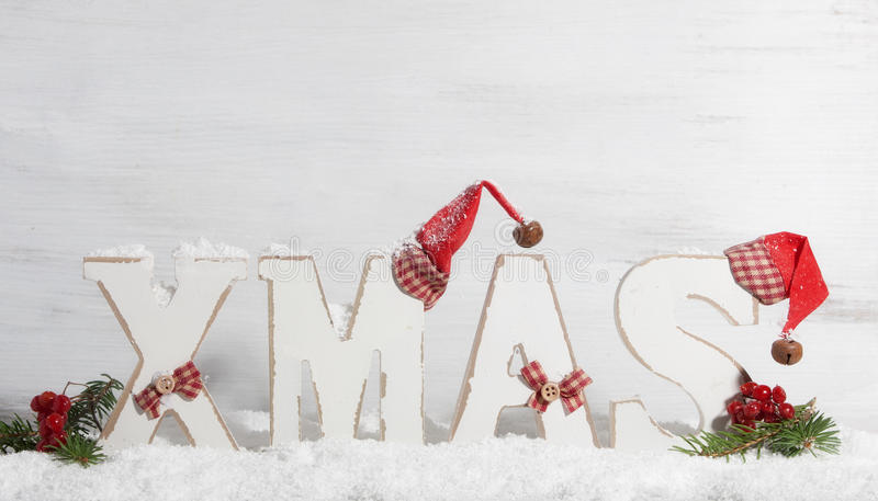 Xmas, Wooden letters with Christmas hats. In front of wooden background royalty free stock image