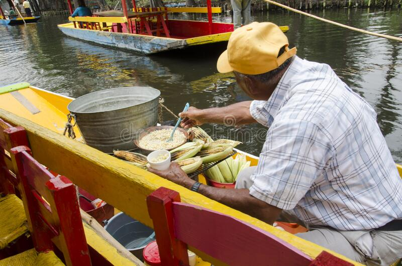 Man preparing esquites and elotes, corn, on a Trajinera boat royalty free stock images