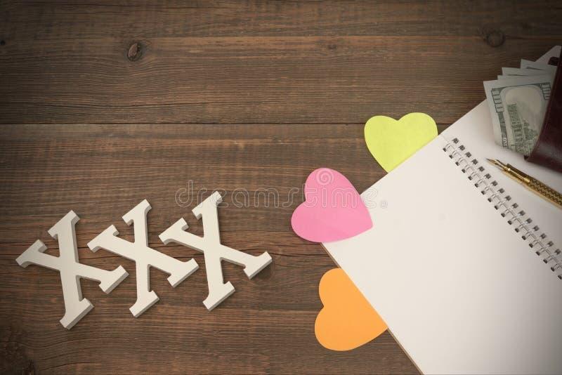 XXX förälskelsetecken, öppnad Notepad och manplånbok med kassa royaltyfri foto