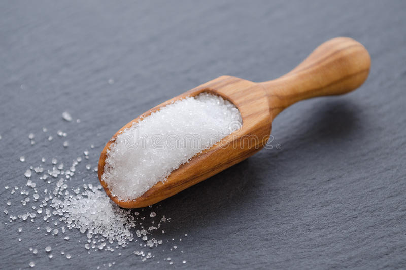 Xylitol or birch sugar in a wooden scoop on black background, selective focus. Birch sugar xylitol in a wooden scoop on black background closeup stock images